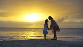 Liten flicka och lycklig moderkontur i solnedgången på stranden stock video