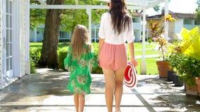 Liten flicka och moder som går i lyxig semesterort på sommarsemester lager videofilmer