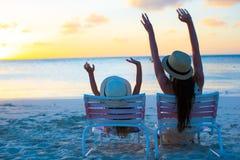 Liten flicka- och modersammanträde på strandstolar på solnedgången Royaltyfri Fotografi