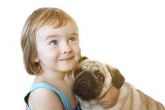 Liten flicka och Mops-hunden på en vit bakgrund royaltyfria foton