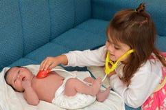 Liten flicka och nyfödd syster Royaltyfri Bild
