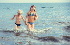 Liten flicka och pojke i havet Arkivfoton