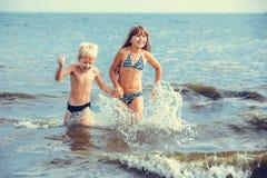 Liten flicka och pojke i havet Royaltyfria Bilder