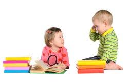 Liten flicka och pojke med böcker arkivfoto