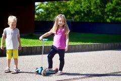 Liten flicka och pojke med en sparkcykel utomhus Fotografering för Bildbyråer