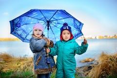 Liten flicka och pojke med paraplyet som spelar i regnet Ungar spelar utomhus- vid regnigt väder i nedgång Höstgyckel för barn st royaltyfri bild