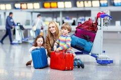 Liten flicka och pojke och barnmoder med resväskor på flygplats arkivbild