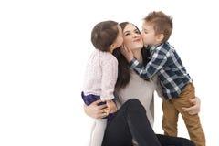 Liten flicka och pojke som kysser deras isolerade moder Arkivfoton