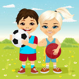 Liten flicka och pojke som rymmer en fotbollboll och basket Arkivbilder