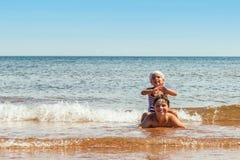Liten flicka och pojke som spelar på stranden Arkivfoton