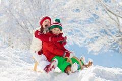Liten flicka och pojke som tycker om släderitt Sledding för barn Litet barnunge som rider en pulka Barnlek utomhus i snö Lurar sl royaltyfri bild