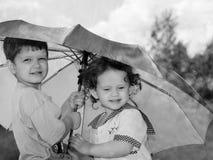 Liten flicka och pojke under ett paraply utanför. Royaltyfri Fotografi