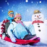 Liten flicka och pojke utomhus Sleding och snögubbebegrepp arkivfoton