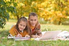 Liten flicka- och pojketeckning med blyertspennor arkivbild