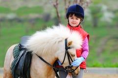 Liten flicka och ponny royaltyfria foton