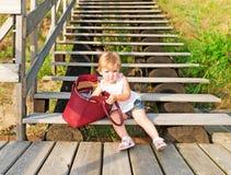 Liten flicka och röd påse Fotografering för Bildbyråer