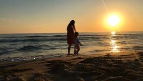 Liten flicka och ung kvinna som promenerar stranden stock video