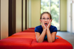 Liten flicka på en bänk i ett soligt rum Fotografering för Bildbyråer