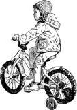 Liten flicka på en cykel Fotografering för Bildbyråer