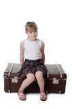 Liten flicka på gammala resväskor Royaltyfri Foto