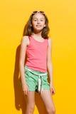 Liten flicka på gul bakgrund Fotografering för Bildbyråer