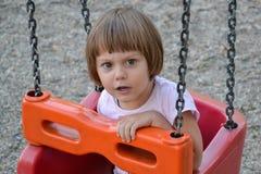 Liten flicka på gunga på lekplatsen Arkivfoton