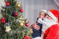 Liten flicka på händerna av Santa Claus royaltyfria foton