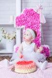 Liten flicka på hennes födelsedag som äter kakan Arkivfoton
