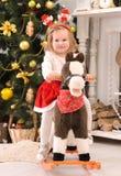 Liten flicka på leksakhäst i inre jul royaltyfri foto