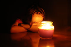 Liten flicka på natten som stirrar på den glödande stearinljuset för Lit royaltyfri fotografi