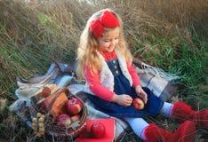 Liten flicka på naturen med en korg av frukt fotografering för bildbyråer