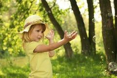 Liten flicka på naturen med såpbubblor Arkivfoto