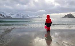 Liten flicka på stranden som ser berg och havet arkivbild