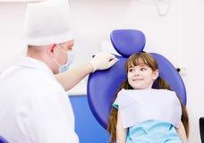 Liten flicka på tandläkares kontor Arkivbild