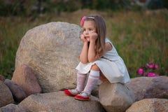 Liten flicka på den stora stenen Royaltyfria Bilder