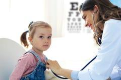 Liten flicka p? doktorn f?r en checkup Manipulera kvinnan auscultate hjärtslaget av barnet royaltyfria foton
