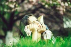Liten flicka p? gr?s i blom arkivfoto