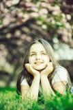 Liten flicka p? gr?s i blom royaltyfria foton