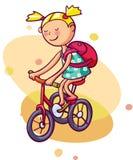 Liten flicka rider en cykel Arkivbilder