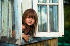 Liten flicka ser ut det lantliga huset för fönstret royaltyfri fotografi