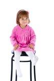 Liten flicka sitter på en hög stol Royaltyfri Bild