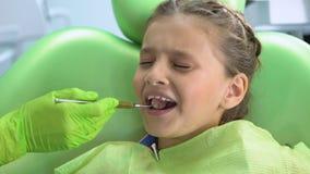 Liten flicka som är rädd av den tand- undersökningen med munspegeln, barnslig skräck, spänning stock video