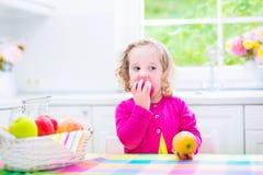 Liten flicka som äter äpplen Arkivbilder