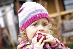 Liten flicka som äter äpplet i höst arkivfoto