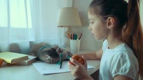Liten flicka som äter äpplet och spelar med hennes husdjurkatt, medan göra läxa arkivfilmer
