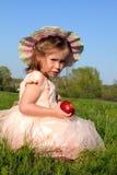 Liten flicka som äter äpplet på äng Royaltyfria Foton