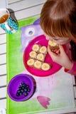 Liten flicka som äter bananbröd för frukost royaltyfri bild