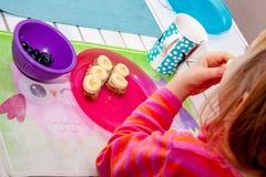 Liten flicka som äter bananbröd för frukost royaltyfria foton
