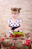 Liten flicka som äter den smakliga jordgubben royaltyfri foto