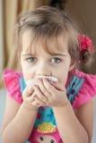 Liten flicka som äter en muffin arkivfoto